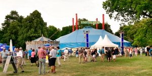 Festplatz und Zirkuszelt mit Besuchern auf einer Wiese